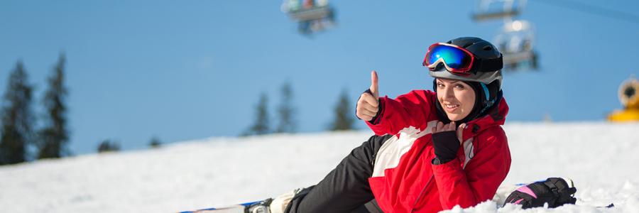 カメラに向かってサムズアップをするスキー中の女性