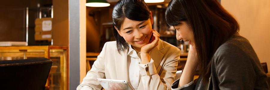 AIによりカフェの混雑状況を把握している女性2人
