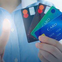 クレジットカードを片手にタッチパネルを操作する女性